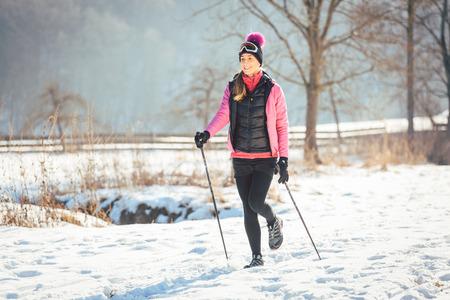 Vrouw op het spoor voor een winterwandeling in zonnig landschap Stockfoto