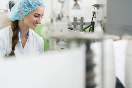 Feliz empleada con sombreros de protección y bata blanca mientras trabajaba como ingeniera de manufactura en una fábrica de cosméticos contemporánea.