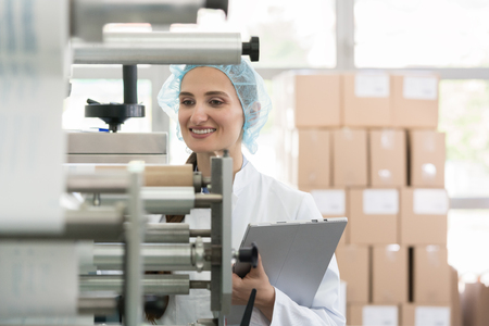 Female manufacturing supervisor looking worried while checking equipment and production during quality control in the interior of a cosmetics factory 写真素材