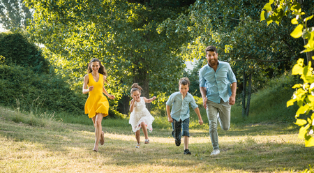 Active young parents with a healthy lifestyle running together with their two competitive children outdoors in a summer day Stock Photo