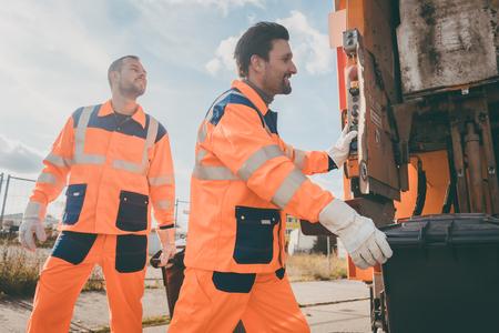 Dwóch śmieciarzy pracuje razem przy opróżnianiu pojemników na śmieci do wywozu śmieci Zdjęcie Seryjne