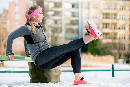 Fit woman stretching her limbs for sports exercise in winter