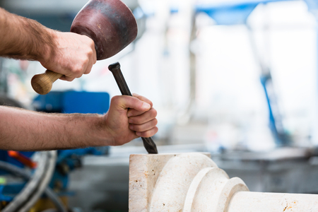 Stone carver working at marble pillar