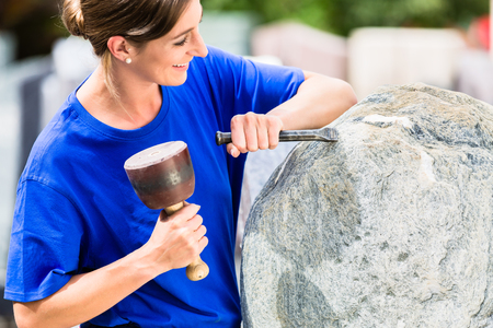 Female stonemason working on boulder with sledgehammer and iron