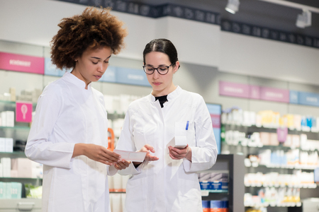 Two experienced female pharmacists wearing lab coats while analyzing together the package of a new pharmaceutical drug in the interior of a modern pharmacy Stock Photo