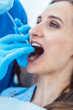 Close-up of the hands of a dentist wearing surgical gloves and using sterile medical equipment, while cleaning the teeth of a young woman in a modern dental clinic
