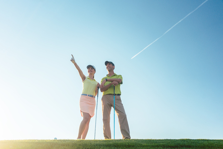 Low-angle view of the silhouette of a man pointing to the horizon, while standing next to his female partner on a professional golf course against sunshine and clear blue sky Stock Photo