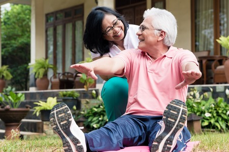 Cheerful senior woman helping her partner during workout session outdoors in the yard