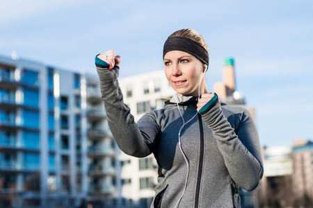 Portrait of a strong young woman practicing boxing exercise while looking forward with confidence and determination outdoors in the city Stock Photo