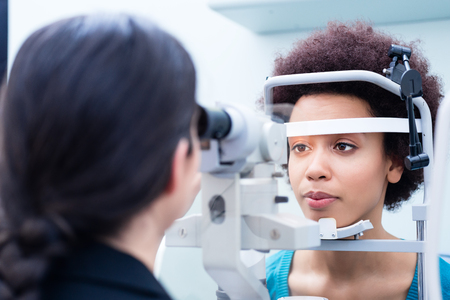 Optician measuring women eyes with refractometer in optician shop
