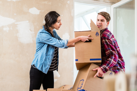 Young woman helping her partner to carry two heavy cardboard boxes while moving in into a new home