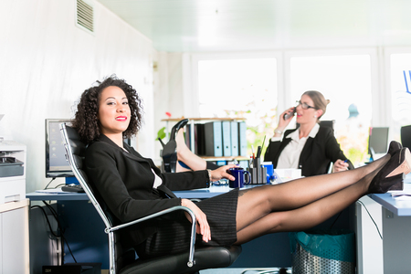 Happy businesswomen relax with their feet on the desk at work