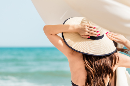 Woman looking from beach to the sea holding her straw hat Stock Photo