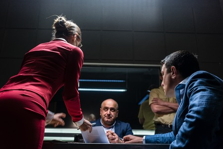 Low-angle view of a female attorney in disagreement with the prosecutor, during the preliminary hearing of an unwilling suspect in the office of a police station