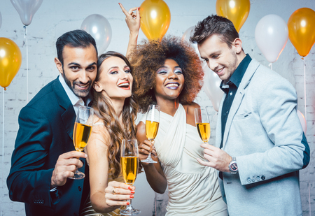 Group of party people celebrating with drinks a birthday or New years eve party