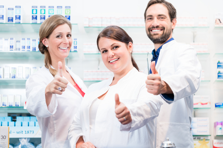 Pharmacists in pharmacy showing thumbs up and smiling