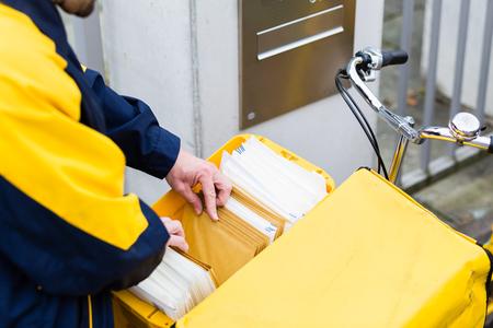 Cartero entregando cartas al buzón del destinatario