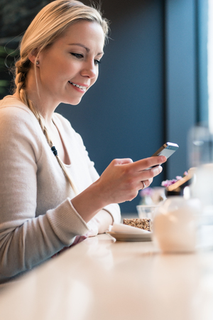 Woman using her phone in a train cabin checking her social media feed Stock Photo