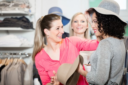 Girlfriends on shopping spree trying ladies hats and other fashion items