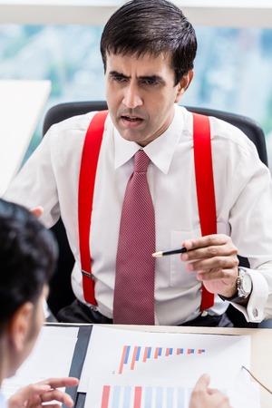 Indian business supervisor talks to subordinate junior professional in office building