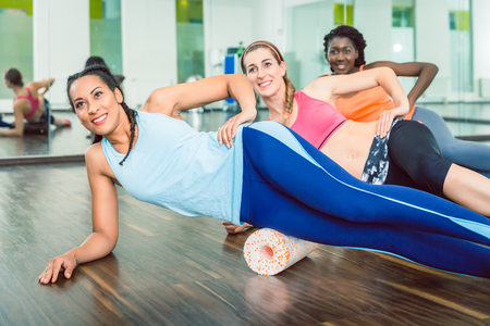 Beautiful fit woman smiling while wearing blue fitness sleeveless top and leggings during group workout class of foam rolling at the gym Stock Photo