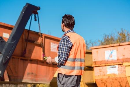 Travailleur sur le chantier de déchargement du conteneur pour les déchets du camion à l'aide de la télécommande