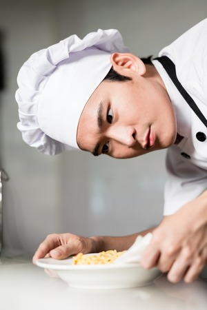 Asian chef plating up a bowl of food carefully wiping around the side to remove any spills, close up on his face with look of concentration Stock Photo