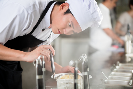 Young Asian chef plating food in a restaurant carefully pipetting garnish onto the side of a plate Foto de archivo