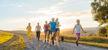 Playful family running and playing on a path in backlit summer landscape