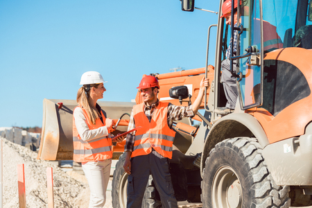 Civil engineer and worker discussion on road construction site, woman and man Stock fotó