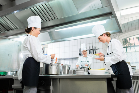 Kitchen brigade in catering kitchen preparing dishes Stock Photo