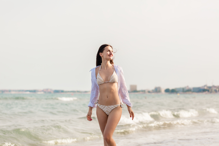 Woman in bikini walking down the beach in her summer vacation along the water