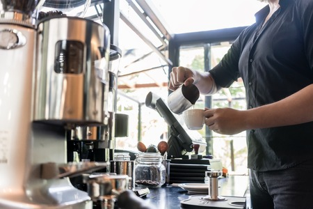 Side view of a young serious bartender pouring fresh milk into a cup of coffee behind the bar counter in a trendy cafeteria