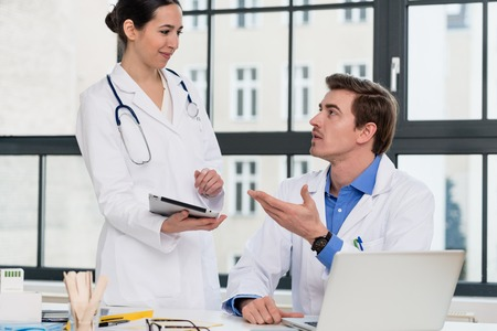 Young female physician using a tablet PC while asking for advice from her experienced male colleague in the office a modern hospital Standard-Bild