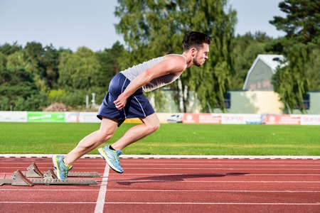 Athlete on cinder track of sports facility at the moment he starts to sprint