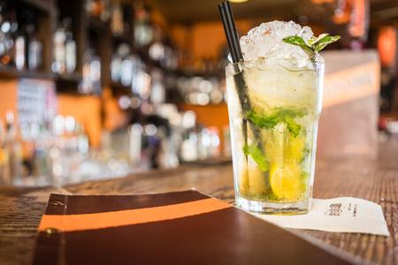 Mojito cocktail and menu on counter of bar