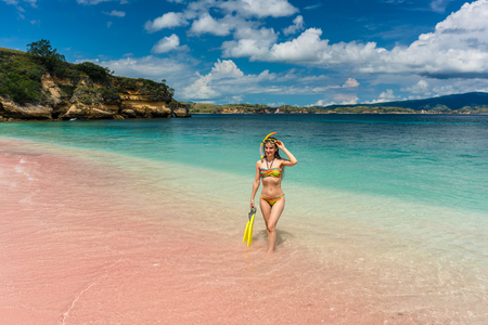 Beautiful young woman smiling while holding snorkeling equipment at Pink Beach during summer vacation in Komodo Island, Indonesia