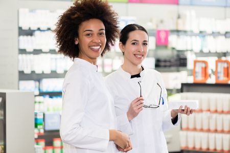 Portrait of a happy African-American young woman looking at camera while working as pharmacist next to her friendly colleague in a modern drugstore