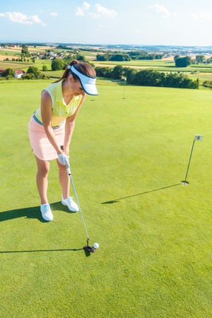 Full length of an attractive fit woman smiling while holding a putter golf club before hitting the ball during professional practice on putting green Stock Photo