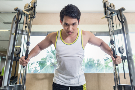 Low-angle view portrait of an Asian handsome man looking down with concentration while exercising cable crossover for chest muscles at the gym