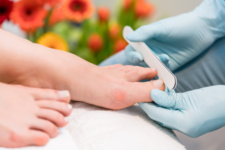Close-up of the hands of a nail technician wearing surgical gloves, while buffing the edges of the toenails of a female client in a modern beauty salon Stock Photo