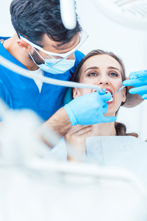 Beautiful young woman looking up relaxed during a painless dental procedure, done by her reliable dentist in a modern clinic with sterile equipment