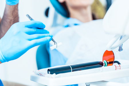 Close-up of the hand of a dentist wearing sterile surgery gloves, while preparing a dental LED curing light machine for treating a patient in a modern clinic