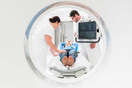 Arzt, Krankenschwester und Patient bei CT-Tomographie im Krankenhaus, Schuss durch die Röhre des Geräts Standard-Bild