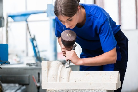 woman Stonemason carving pillar out of stone in her workshop