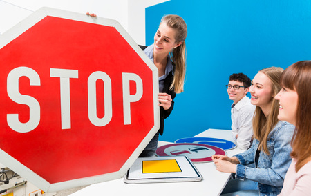 Driving teacher explaining meaning of street signs to class of students Stock Photo