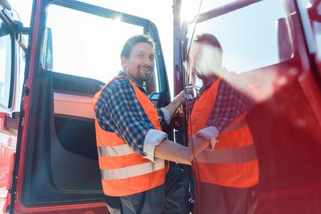 Conductor de camión frente a su camión de larga distancia entrando
