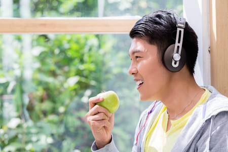 Side view close-up portrait of a young man eating a fresh green apple while listening to stereo headphones indoors