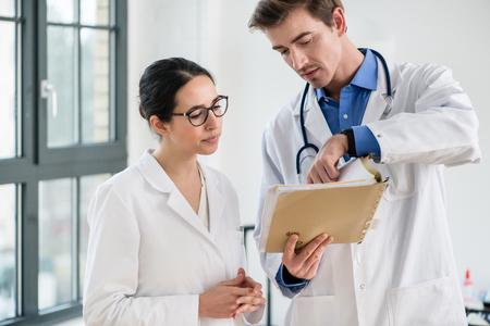 Dos médicos dedicados que verifican la información del historial médico de un paciente en el interior de un hospital moderno.