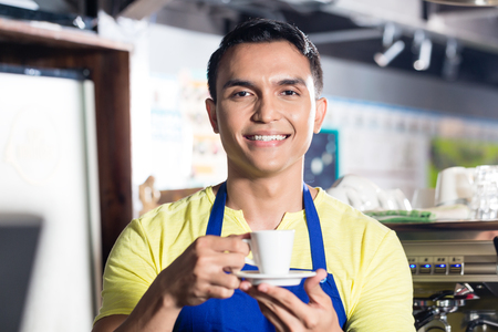 Male barista in Indian cafe, holding espresso cup with coffee in hands Stock Photo